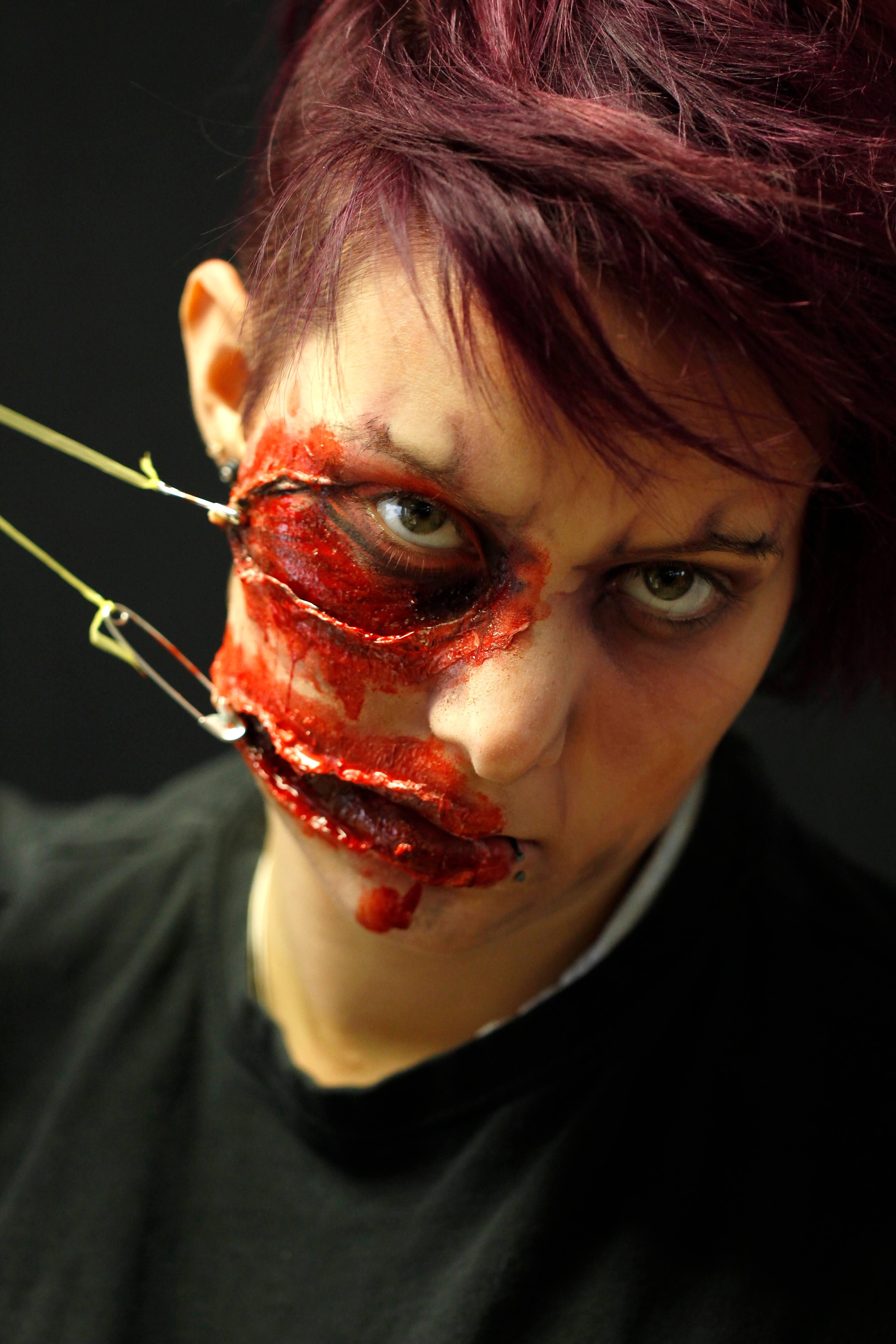 Maquillage de zombie pour Halloween avec des épingles à nourrisses qui arrachent l'oeil et la joue