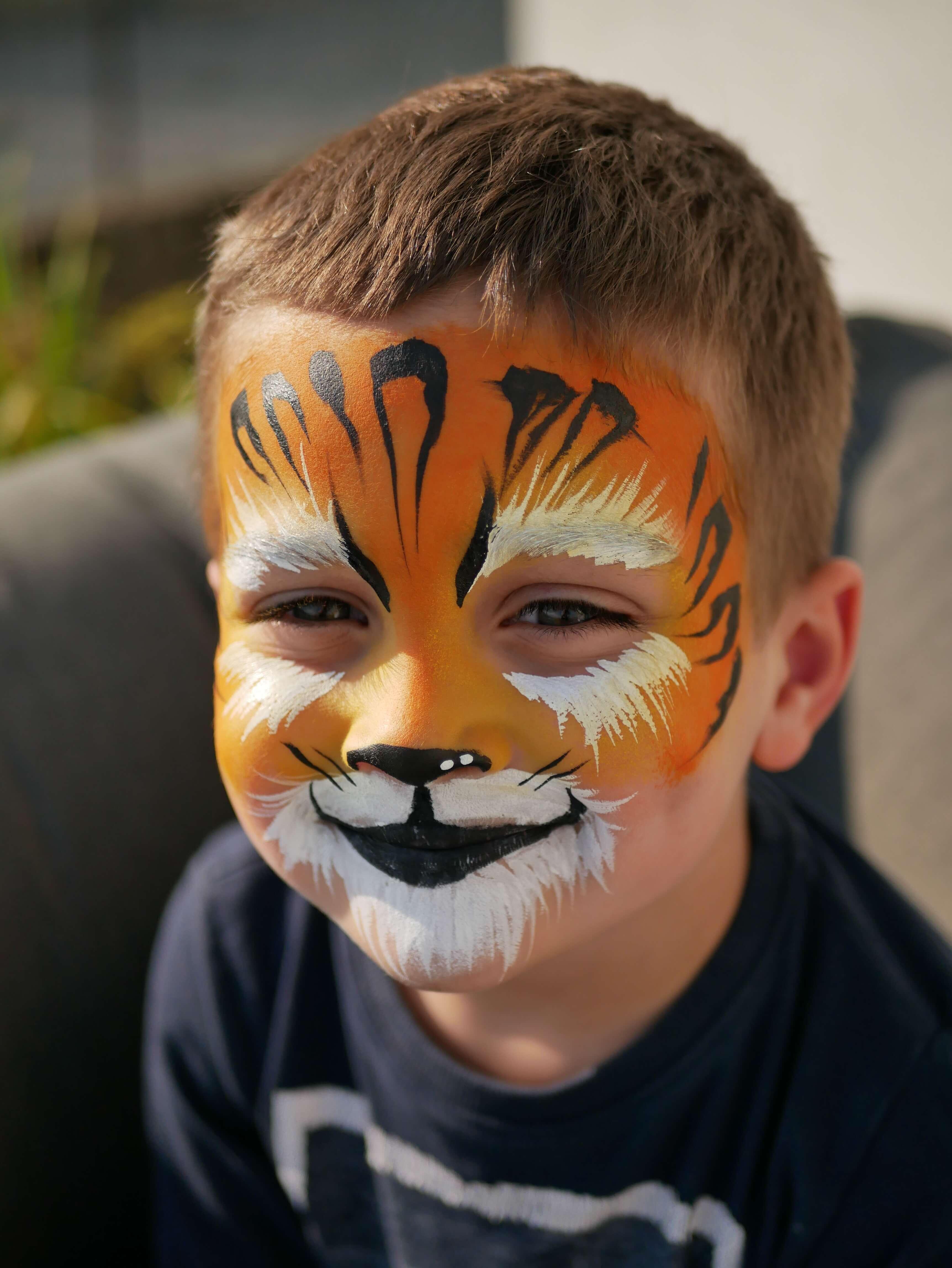 Petit garçon grimé en tigre avec du fard à l'eau